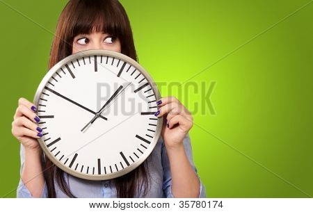 A Young Girl Holding A Clock On Green Background