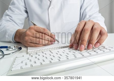 Doctor Typing On Wireless Computer Keyboard In Office. Physician In White Medical Gown Works With Co
