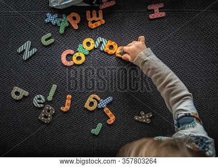The Corona Menace In Colorful Letters With A Little Boy Who Crashes The Typography With His Toy Car.
