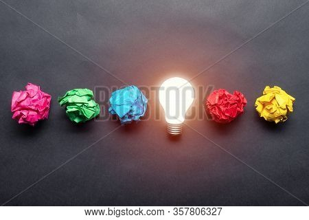 Lightbulb And Crumpled Colorful Paper Balls On Black Background. Successful Solution Of Problem. Ide