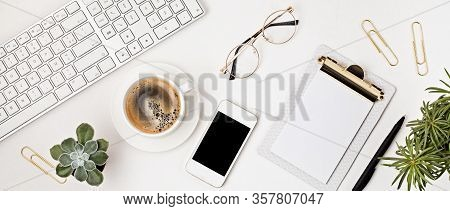 Top View Of Office Desk. Table With Keyboard, Smartphone, Clipboard And Office Supplies. Flat Lay Ho