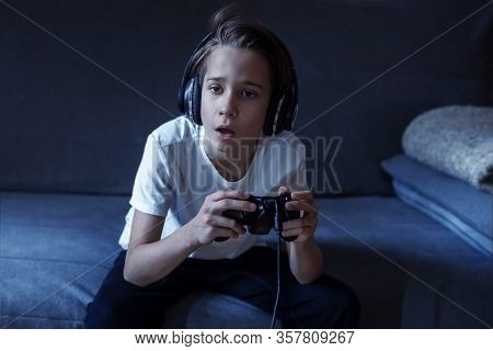 The Boy Is Sitting On The Couch And Holding A Joystick, Playing Video Games, Addiction To The Game C