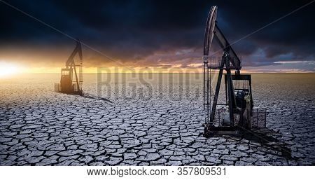 Oil rig in the desert on a background of a dramatic sky. Symbol of the crisis in the oil industry