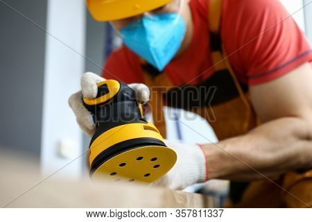 Male Construction Worker Wearing Hardhat And Protective Mask Using Hand Electrical Sanding Machine C