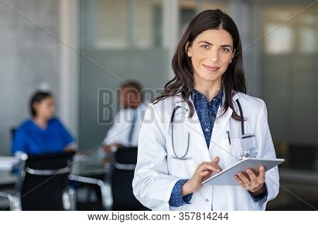 Portrait of beautiful mature woman doctor holding digital tablet and looking at camera. Confident female doctor using digital tablet with colleague talking in background at hospital. Latin nurse.