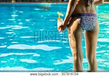 Beautiful Young Woman, Rear View, Standing With Cocktail Near The Pool In Hot Summer Day