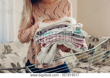 Happy Woman Housewife Gathered Clean Clothes From Dryer In Heap. Housekeeping And Household Chores.