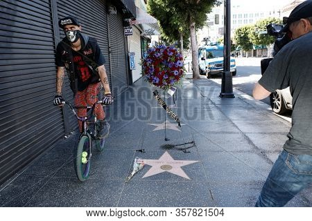 LOS ANGELES - MAR 21: A man with a protective mask cycles by as a wreath is placed at the star of Kenny Rogers on the Hollywood Walk of Fame on March 21, 2020 in Los Angeles, CA.