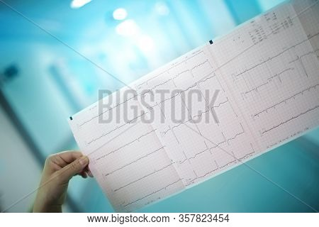 Ecg Chart In Doctors Hands Against The Long Hospital Corridor.