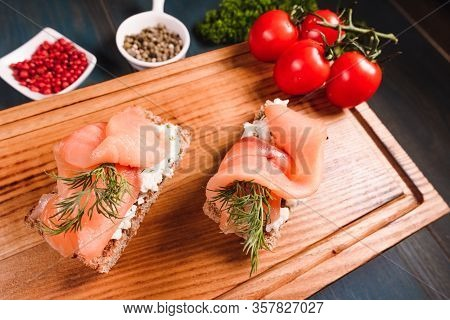 Appetizing Sandwiches With Red Fish And Cheese Lie On A Wooden Tray, Among The Seasonings. Studio Ph