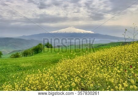 landscape of Sicily with snowy Etna Mount above cloudscape