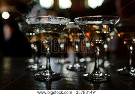 Martini Glasses Stand On A Wooden Stand. Martini Glasses Are On The Bar. Clean Glasses With Alcohol.