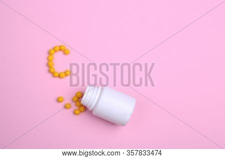 Vitamins Are Scattered On A Pink Background Like The Letter C