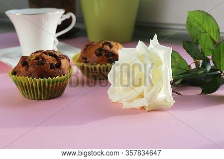 A White Rose Lies On A Table Near Cupcakes And A Cup
