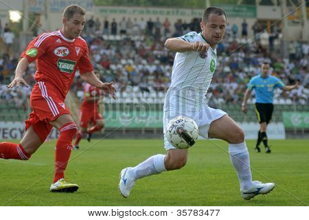 KAPOSVAR, HUNGARY - AUGUST 4: Nikola Safaric (in white) in action at a Hungarian National Championship soccer game Kaposvar (white) vs Debrecen (red) August 4, 2012 in Kaposvar, Hungary.