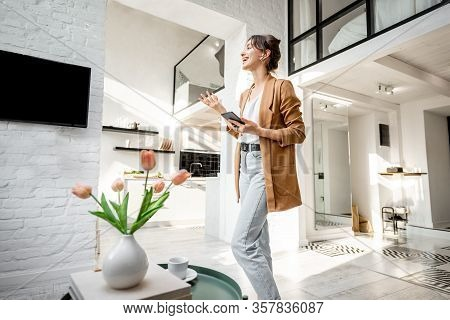 Woman Having Some Business Work, Standing With A Smart Phone In The Modern Living Room At Cozy Home.