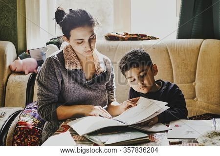 Parenting Help With Homework. Authentic Photo Of Young Mother Helping Her Little Boy Do Homework