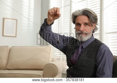 Psychotherapist With Pendulum In Office, Space For Text. Hypnotherapy Session
