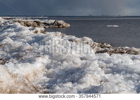 Ice Hummocks On The Shore Of The Gulf Of Finland In Early Spring, St. Petersburg In The Background,