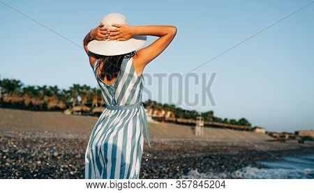 Horizontal Rear View Image Of Brunette Beautiful Woman With White Hat, Walking Along The Beach At Se