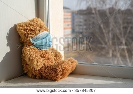 A Teddy Bear In A Medical Protective Mask Sits On A Windowsill And Looks Out The Window. Sadness And