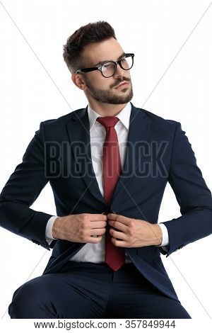 young businessman wearing glasses sitting and unbuttoning his jacket with tough attitude on white studio background