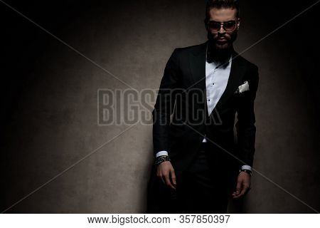 sexy businessman wearing sunglasses standing and looking at camera tough on dark studio background
