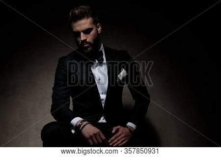 handsome businessman wearing black tuxedo sitting and posing tough on dark studio background