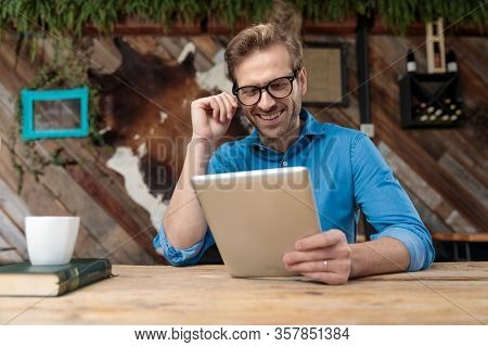 casual man wearing glasses sitting at desk and looking at his tablet happy at the coffeeshop