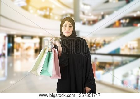 Arabian Woman Standing In Hall Of The Mall. Arabic Woman Wearing Abaya And Holding Shopping Bags.