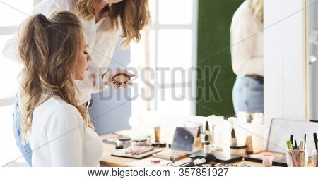 Make-up artist doing make up for young beautiful bride applying wedding make-up