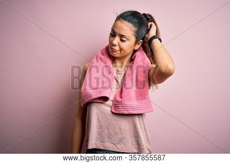 Young beautiful brunette sportswoman wearing sportswear and towel over pink background confuse and wondering about question. Uncertain with doubt, thinking with hand on head. Pensive concept.