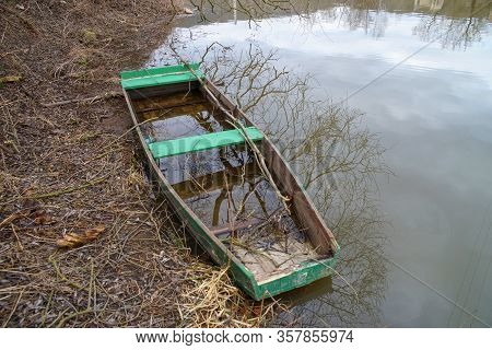 Sunken Green River Boat With Reflection Of Sky And Trees.