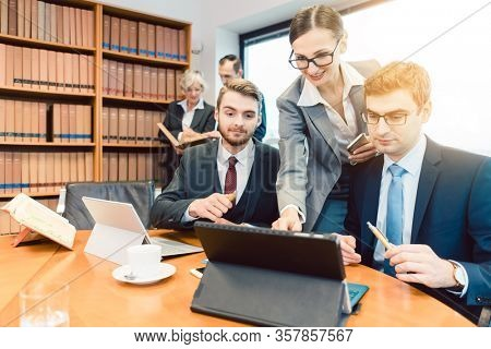 Young but diligent Lawyers in their law firm working on computer with books in background