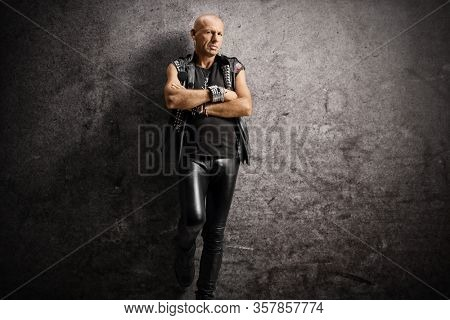 Serious bald punk leaning on a rusty wall and posing with crossed arms