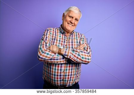 Senior handsome hoary man wearing casual colorful shirt over isolated purple background happy face smiling with crossed arms looking at the camera. Positive person.