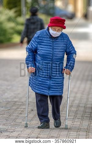 Ruzomberok, Slovakia - March 26: Senior With Protective Face Mask Amd Crutches Walking In City On Ma