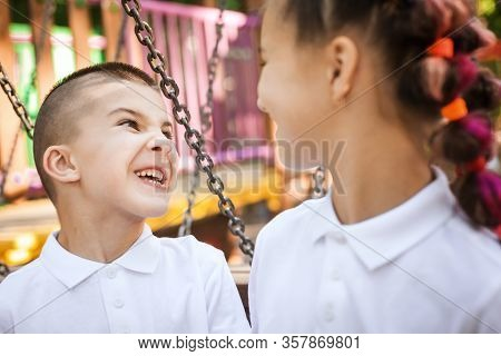 Happy Small Boy Looking At A Pretty Girl Sitting At The Playground. Concept Of Summer, Childhood And