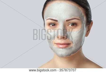 Beautician Makes A Face Clay Mask Against Acne On The Face Of A Woman To Rejuvenate The Skin.treatme