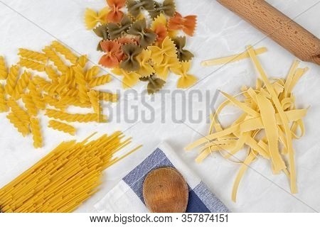 Raw Pasta On The Kitchen Table With Dishcloth Wooden Board Knife And Copy Space