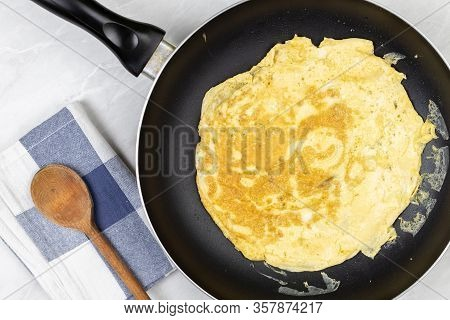Flatlay Above Fried Omelet In The Frying Pan With Dishcloth On The Table