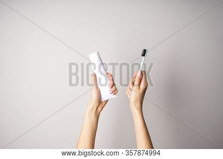 Morning Concept, Toothpaste And Toothbrush In The Hands Of A Young Woman On A Gray Background.