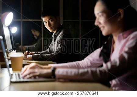 Young adult asian businessman and woman working late at night in their office with desktop computer and laptop. Using as hard working and working late concept.