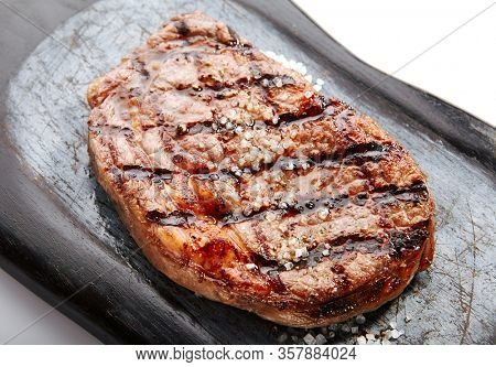 Ribeye steak with salt and spices. Served roasted meat close up view. Grilled beef in plate. Restaurant delicious food. Fried cow rib eye. Barbecue dinner, gourmet meal. Smoked pork piece