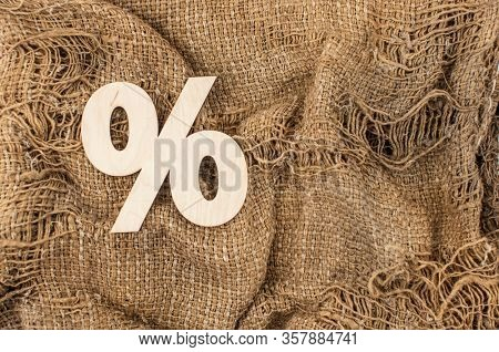 Wooden sign percent on background of burlap hessian sacking