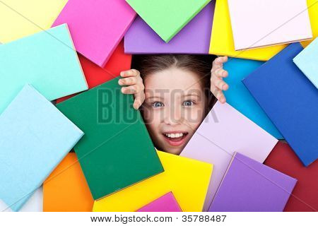 Discovering the wonderful world of knowledge - amazed young girl emerging from beneath colorful books