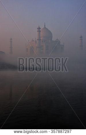 View Of Taj Mahal Reflected In Yamuna River With Early Morning Fog, Agra, Uttar Pradesh, India. Taj