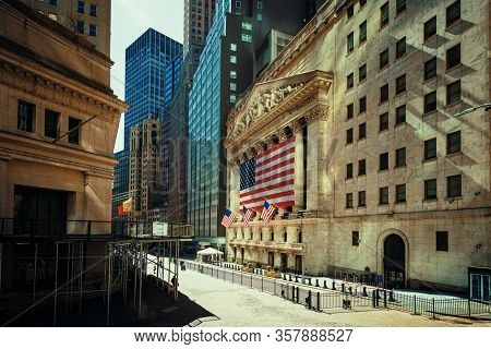 NEW YORK, USA - MARCH 21, 2020: Empty Wall Street with few pedestrians and traffic as the result of COVID-19 coronavirus pandemic outbreak in New York City.