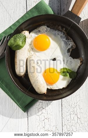 Fried Eggs, Sausage In Iron Pan -  Healthy Food English Breakfast. Colorblock. Homemade Breakfast Wi