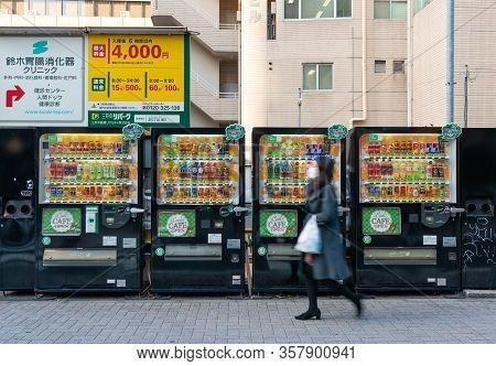 Tokyo, Japan - Mar 15, 2019: Woman Wearing Face Mask Walking Past Row Of Vending Machines In Tokyo
